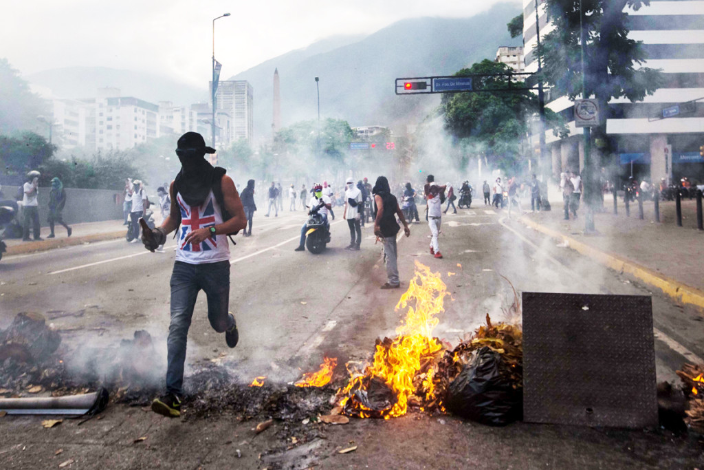 """A group of people protest during an opposition march April 22 in Caracas, Venezuela. In response to a renewed constitutional crisis in the country, the Venezuelan bishops' conference has called for """"peaceful civil disobedience"""" to restore constitutional order. (CNS photo/Miguel Gutierrez, EPA)"""