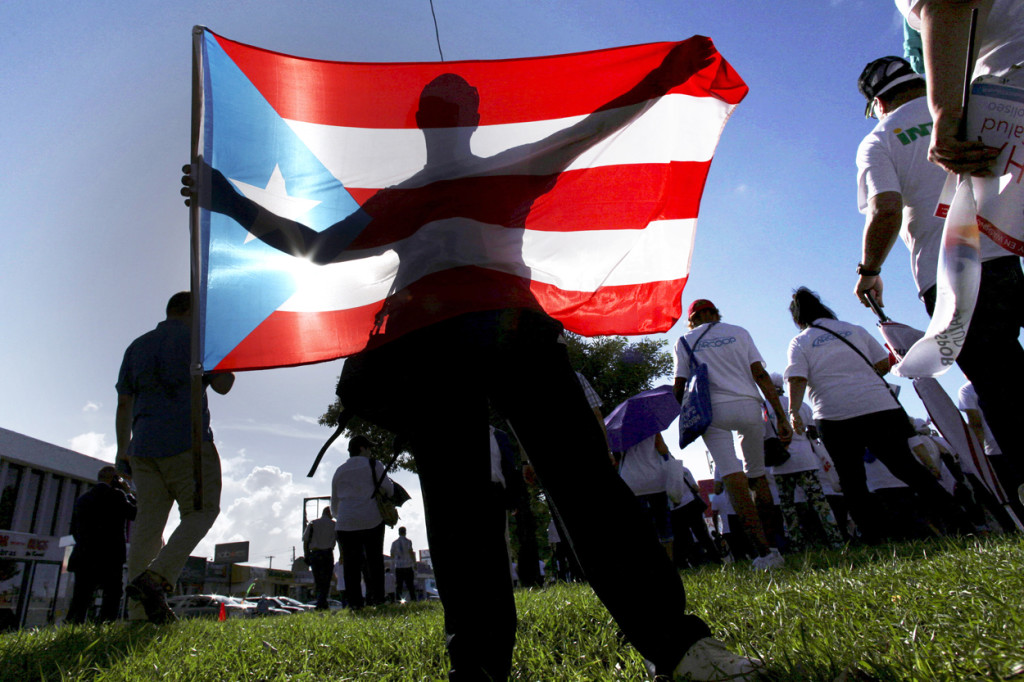 A protester holds a Puerto Rican flag during a march to improve healthcare benefits in San Juan, Puerto Rico, Nov. 5, 2015. An oversight financial board filed paperwork May 3 to protect the U.S. territory from creditors, allowing Puerto Rico to begin to restructure its $72 billion debt. (CNS photo/Alvin Baez, Reuters) See PUERTO-RICO-BANKRUPTCY May 5, 2017.‏
