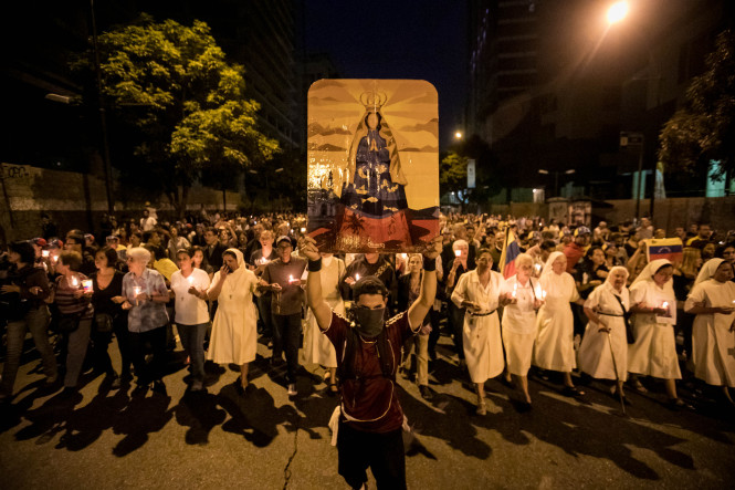 A man holds an image of Mary during a vigil in honor of 17-year-old protester Neomar Lander June 8,the latest fatality during anti-government demonstrations and clashes with security forces in Caracas, Venezuela. (CNS photo/Miguel Gutierrez, EPA) Reuters) See POPE-VENEZUELA June 8, 2017.