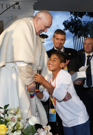 Pope Francis greets a boy outside the Apostolic Nunciature in Bogota, Colombia, Sept. 6. The pope plans to visit four Colombian cities during his six-day trip. (CNS photo/Paul Haring) See POPE-COLOMBIA-ARRIVE Sept. 6, 2017.