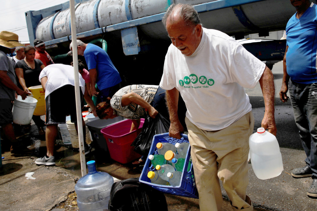 A man carries containers filled with water from a tank truck in Canovanas, Puerto Rico, Sept. 26. (CNS photo/Carlos Garcia Rawlins, Reuters) See PUERTO-RICO-UPDATE Sept. 27, 2017.