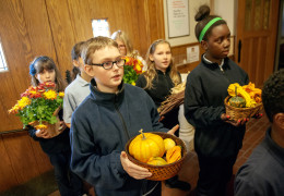 Holy Cross School fifth-graders Joseph Ashmead and Marguerite Kasinge join classmates in bringing Thanksgiving offerings to the altar during a Nov. 24 Thanksgiving Mass at Holy Cross Church in Rochester, N.Y. (CNS photo/Mike Crupi, Catholic Courier)