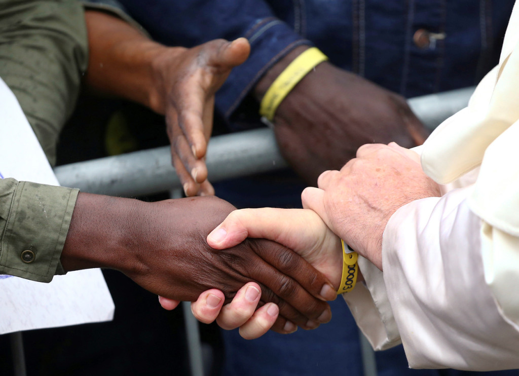 Pope Francis shakes hands with a man as he visits a migrant reception centre during a pastoral visit in Bologna, Italy, Oct. 1. The pope is seen wearing a yellow ID bracelet with his name and a number, just like the immigrants and refugees at the center. (CNS photo/Alessandro Bianchi, Reuters) See POPE-CESENA-BOLOGNA Oct. 2, 2017.