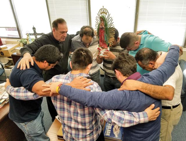El padre José E. Hoyos, director de la Oficina de Apostolado de la Diócesis de Arlington, Virginia, ora con un grupo de líderes hispanos. (Foto CNS / Mary Stachyra Lopez, Arlington Catholic Herald).