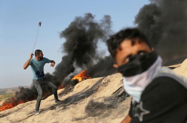 Un manifestante palestino lanza una piedra contra soldados israelíes durante los choques en la frontera entre Israel y la Franja de Gaza.